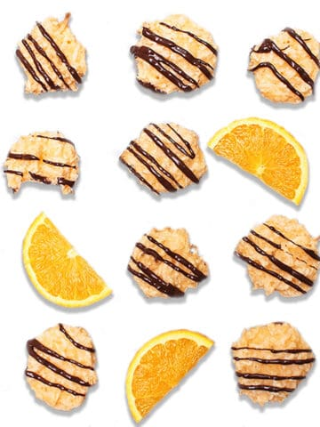 Overhead of drizzled cookies with orange slices on white table.