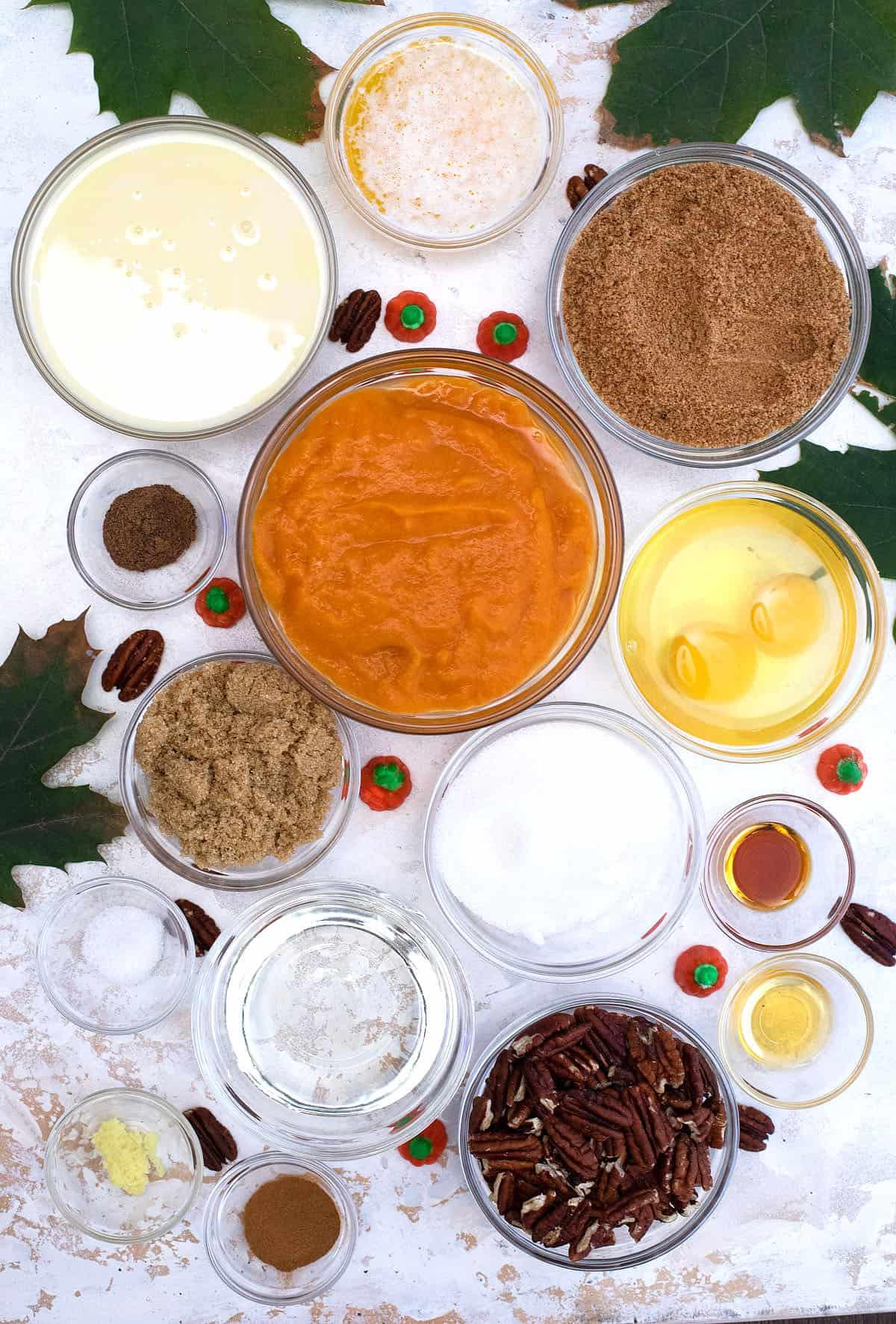 Pumpkin Pecan Pie ingredients on white marbled table.