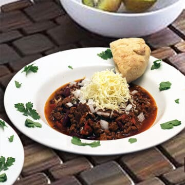 Bowl of hearty chili topped with cheese on brick surface.