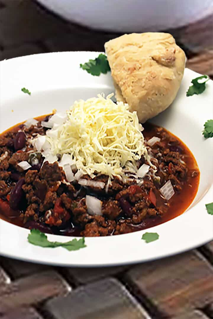 Chili in white bowl with parsley garnish and slice of bread.