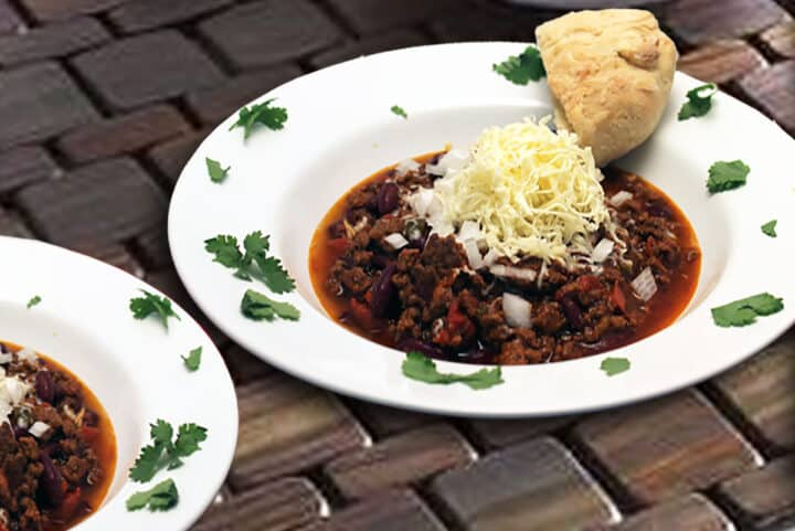 Serving of hearty beef chili in white bowl on brick surface.
