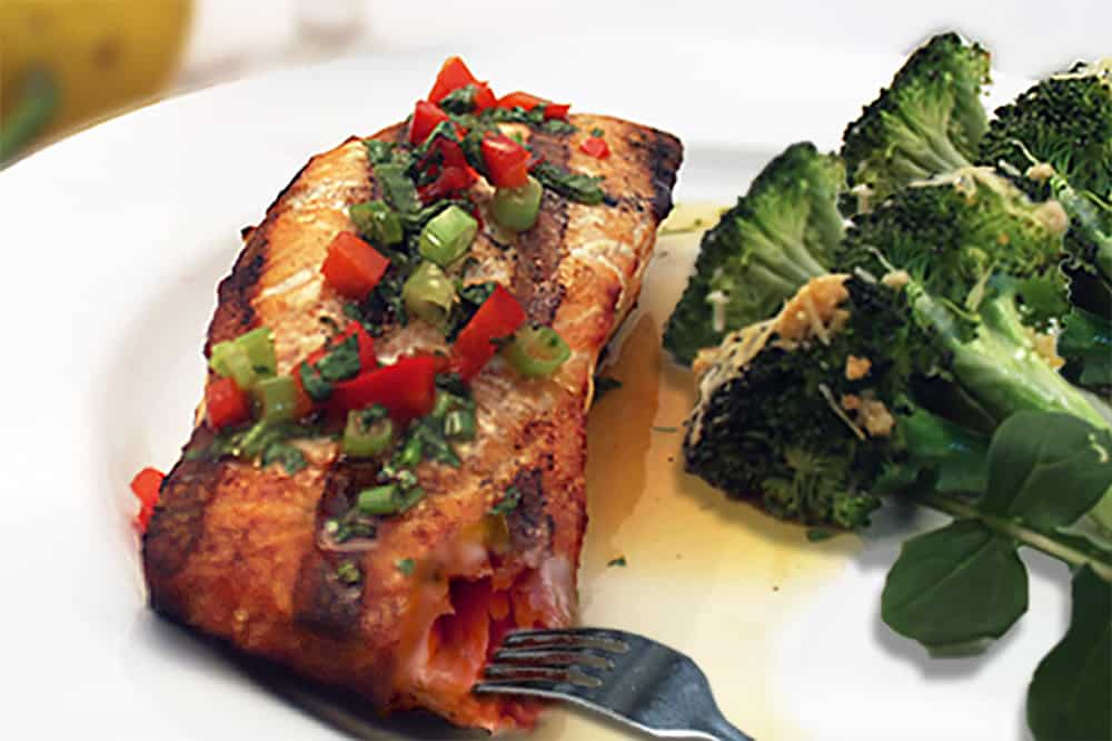 Showing inside of pink flaky salmon with broccoli.