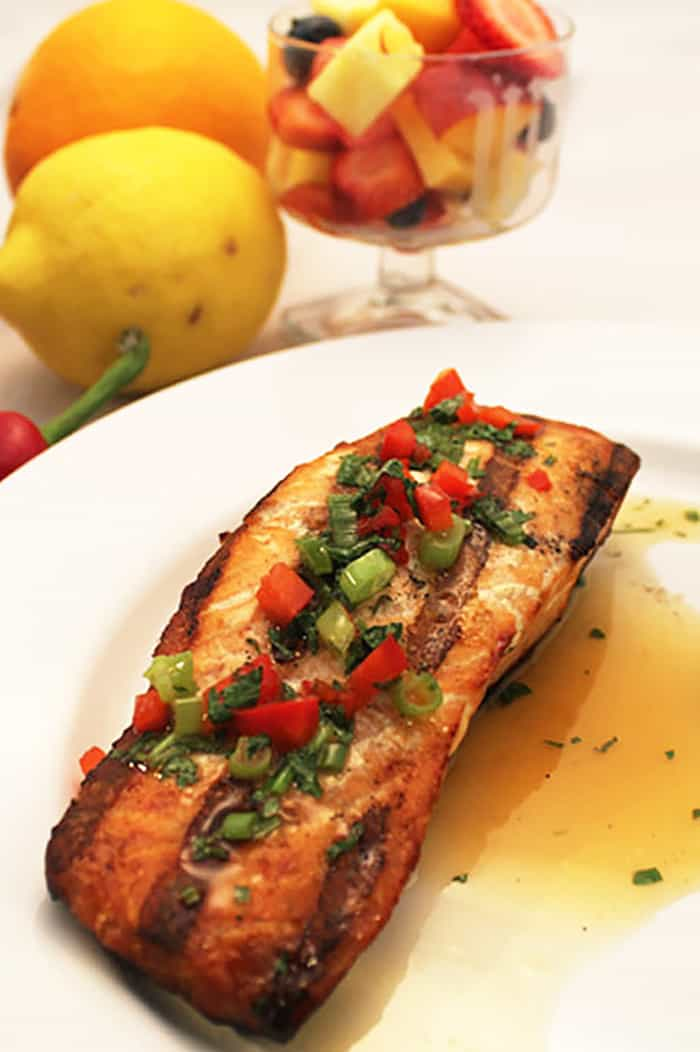 Grilled Salmon drizzled with orange sauce on white plate with fruit in background.