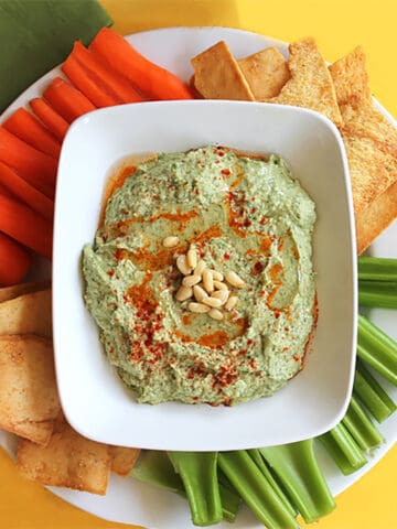 Closeup overhead of hummus in white serving bowl with dippers like celery and carrots around it.
