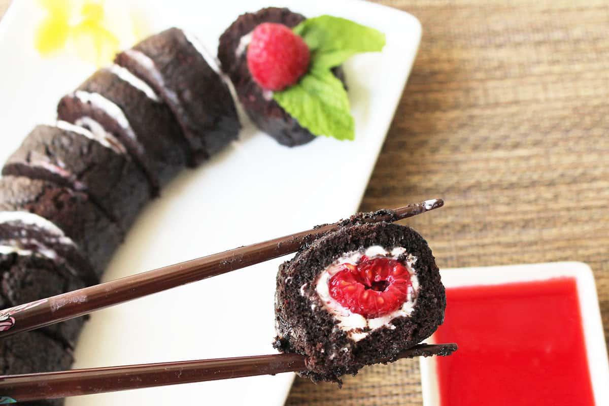 Holding slice of Chocolate Raspberry Dessert on chopsticks.
