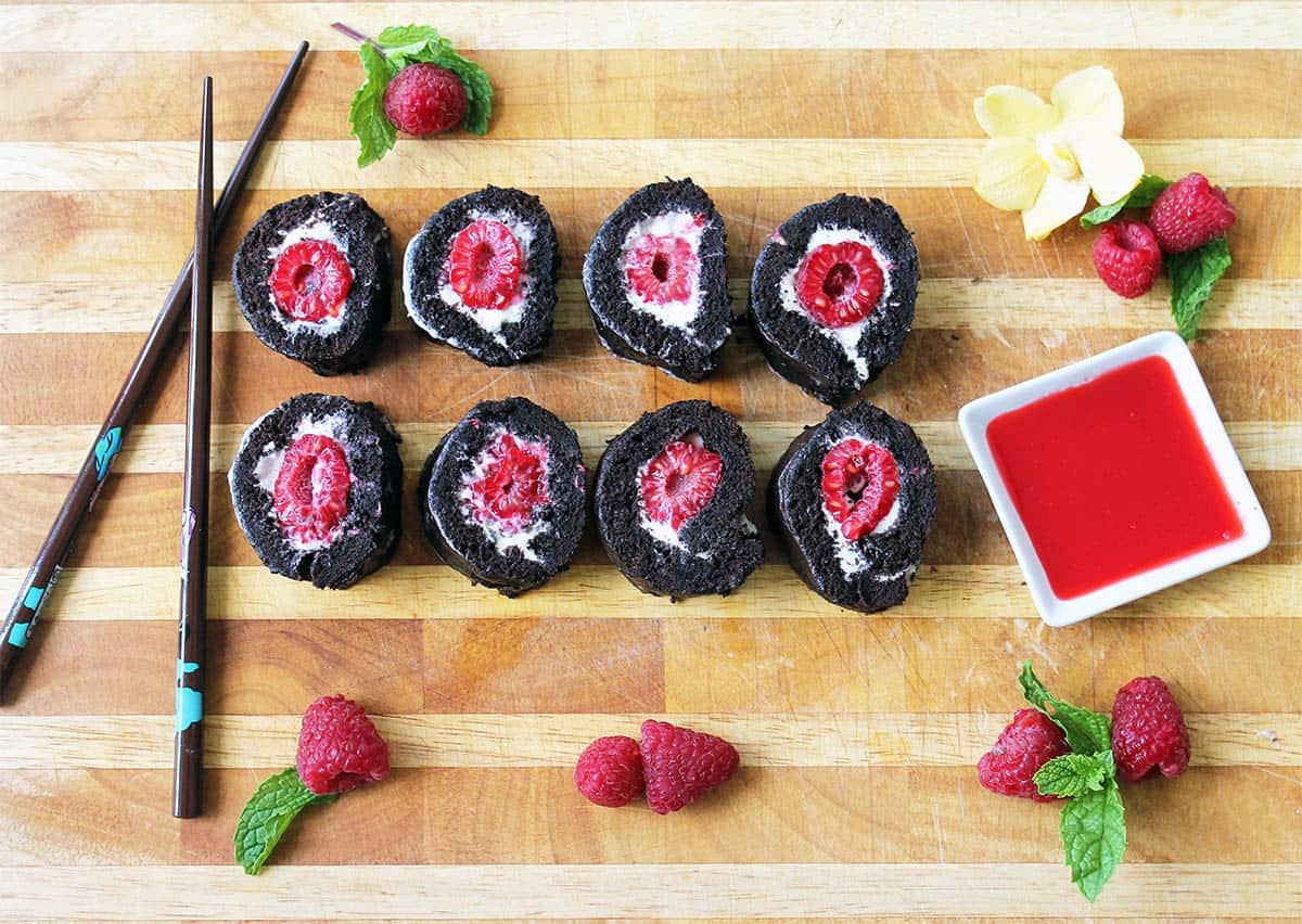 Overhead of sliced raspberry dessert on wooden board.