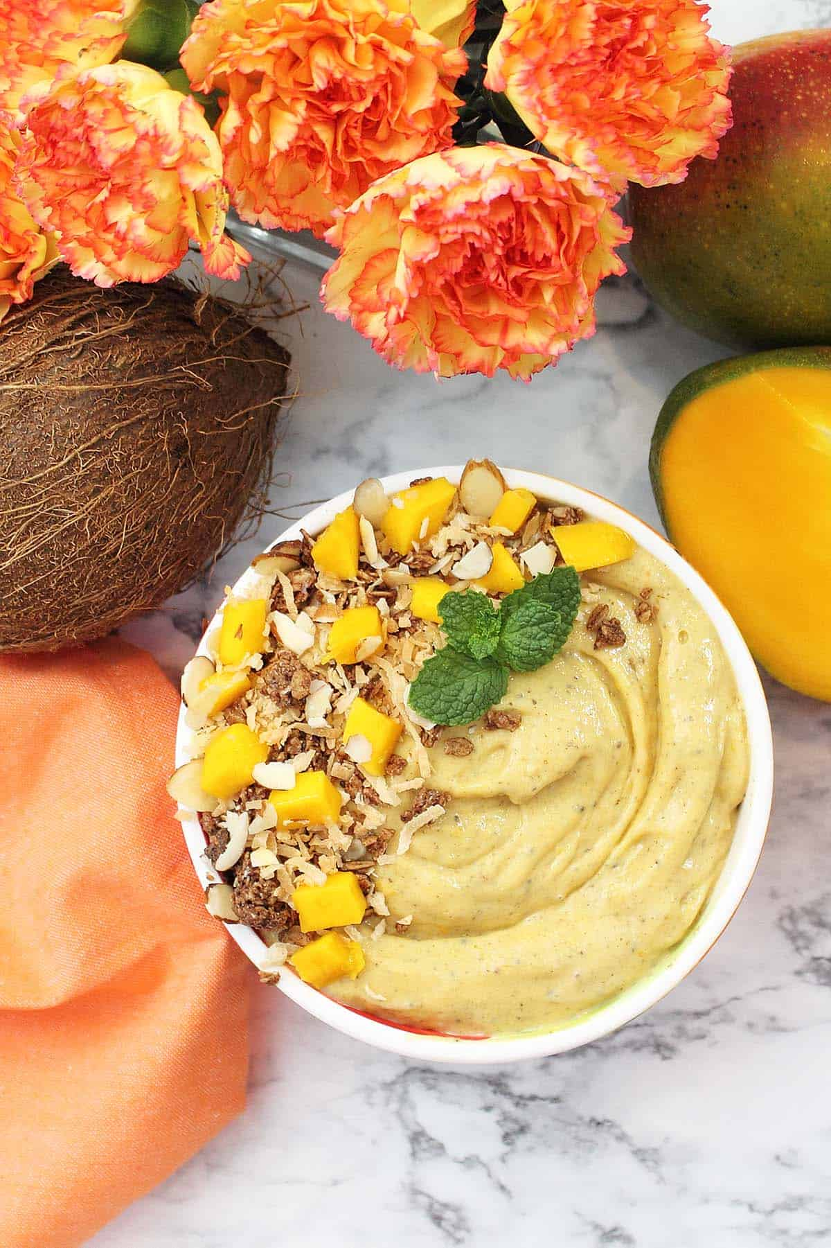 Overhead of smoothie bowl with coconut, mangoes and flowers around it