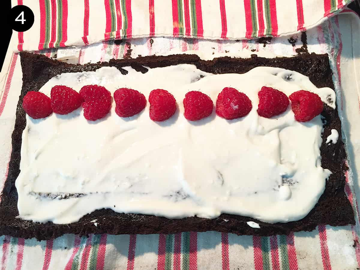 Spreading filling on cake and adding a row of raspberries step 4.