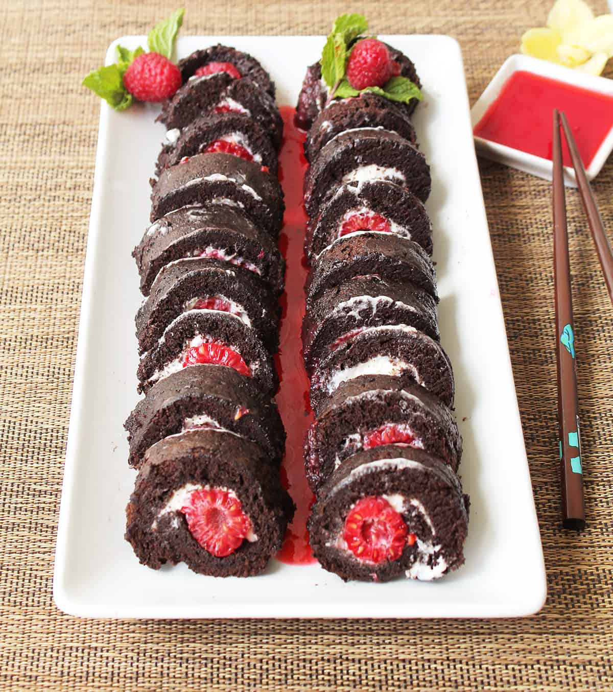Two chocolate raspberry sushi rolls on white platter with raspberry sauce.