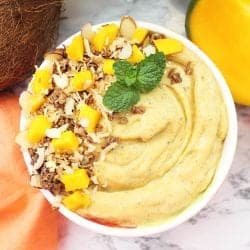 Closeup of smoothie in white flowered bowl with garnishes of coconut mango and granola.