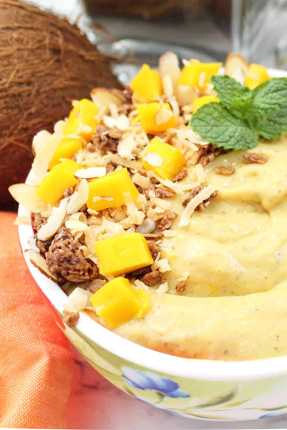 Partial side view of mango smoothie bowl garnished with coconut granola and diced mango.