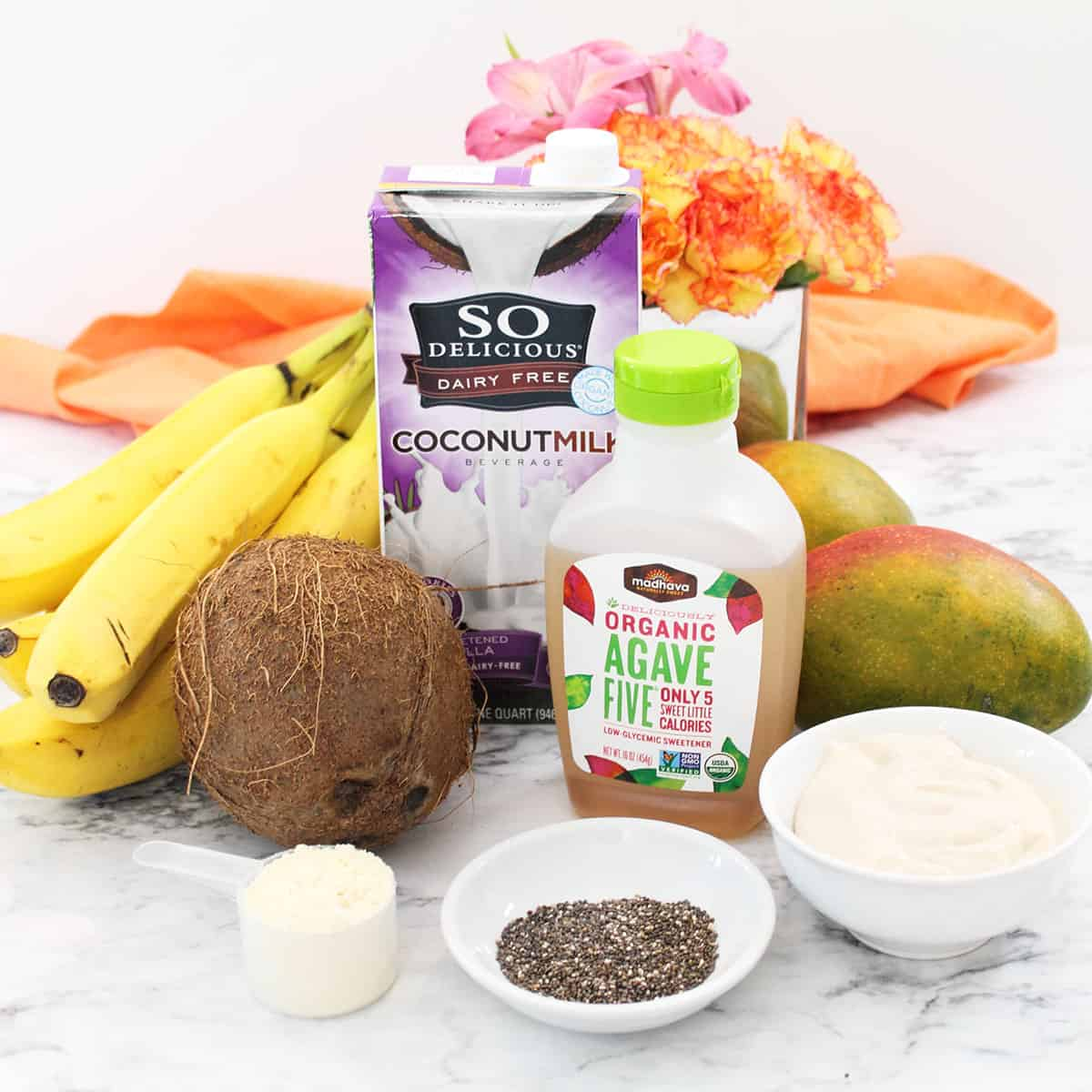 Smoothie ingredients laid on white table.