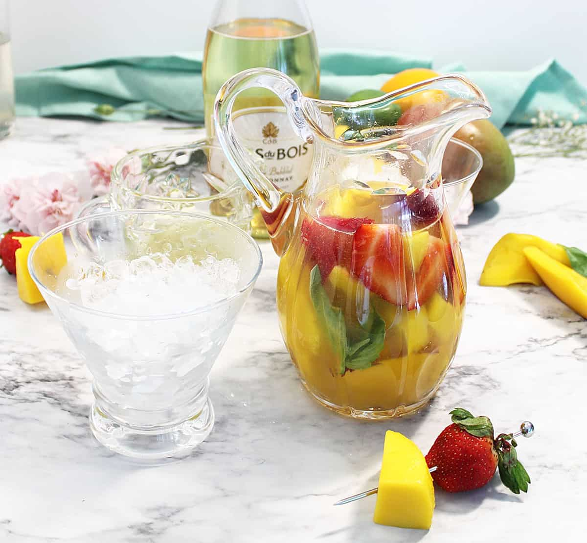 Mango Basil Cocktail in pitcher on white table.