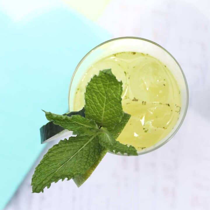 Overhead looking into inside of glass with cucumber and mint garnish.