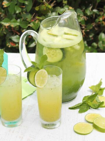 Pitcher of Cucumber Cocktails with two filled glasses in front and lime and mint on table.