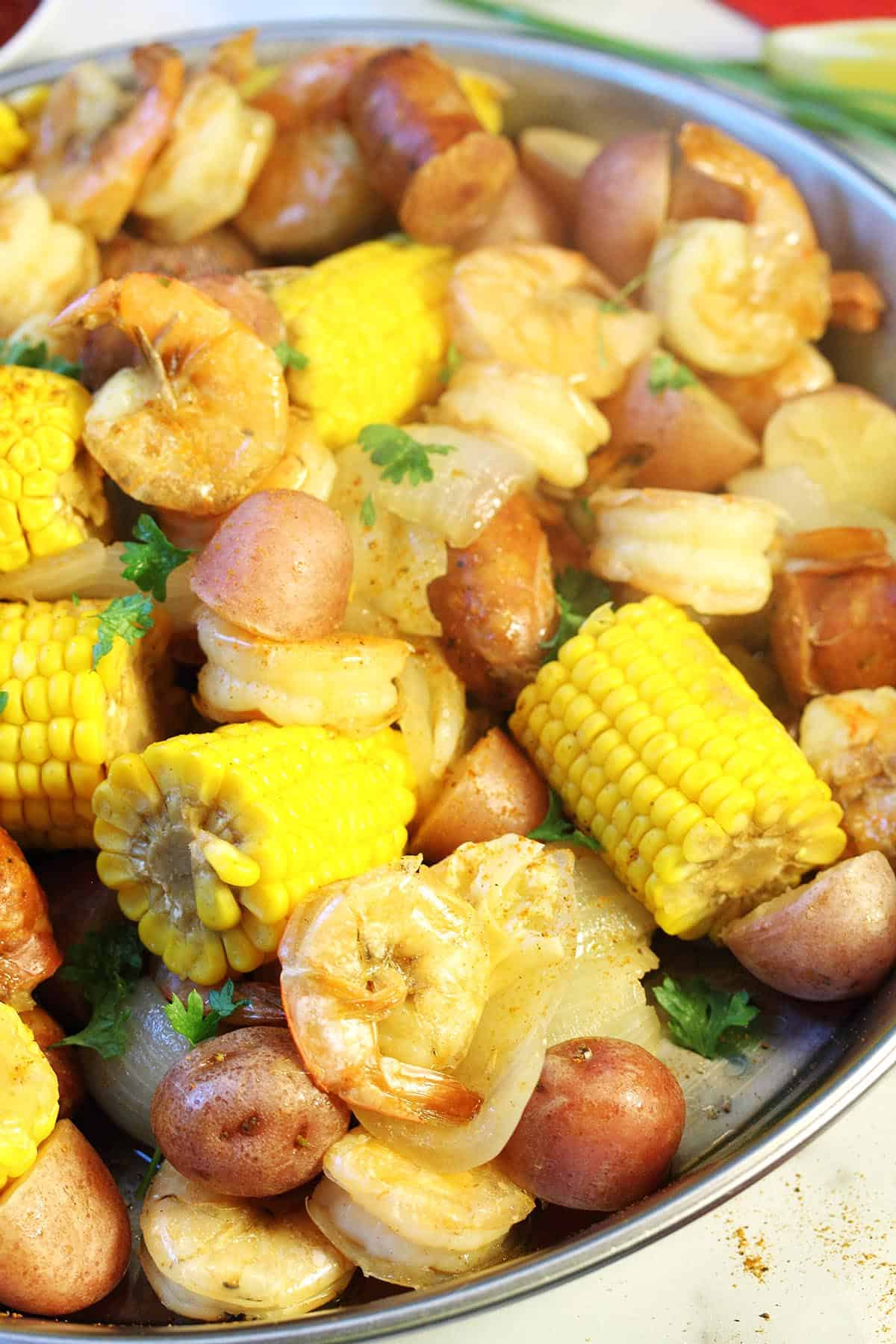 Closeup of boil in round pan showing corn shrimp and potatoes.
