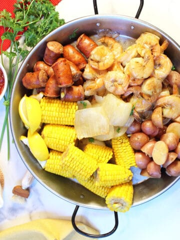 Overhead showing each seafood boil ingredient in round pan.