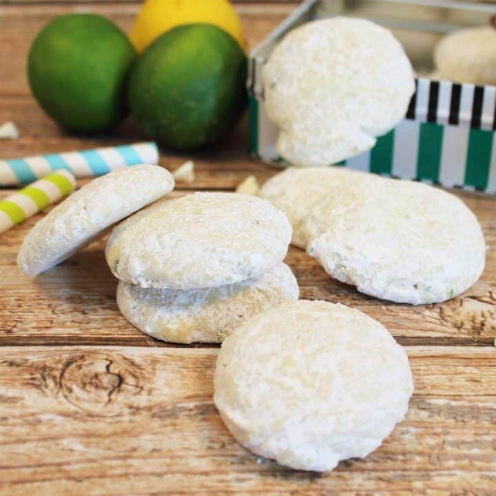 Closeup of cookies on wooden table with cookie tin and limes.