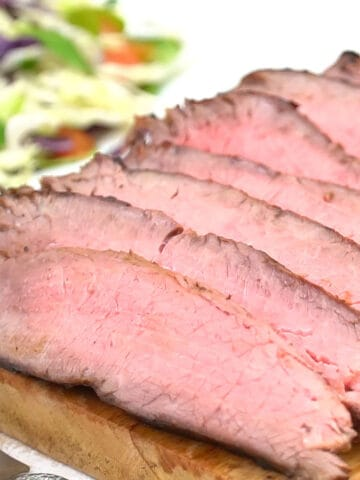 Closeup of sliced flank steak on cutting board.