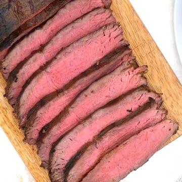 Overhead of sliced steak on carving board.