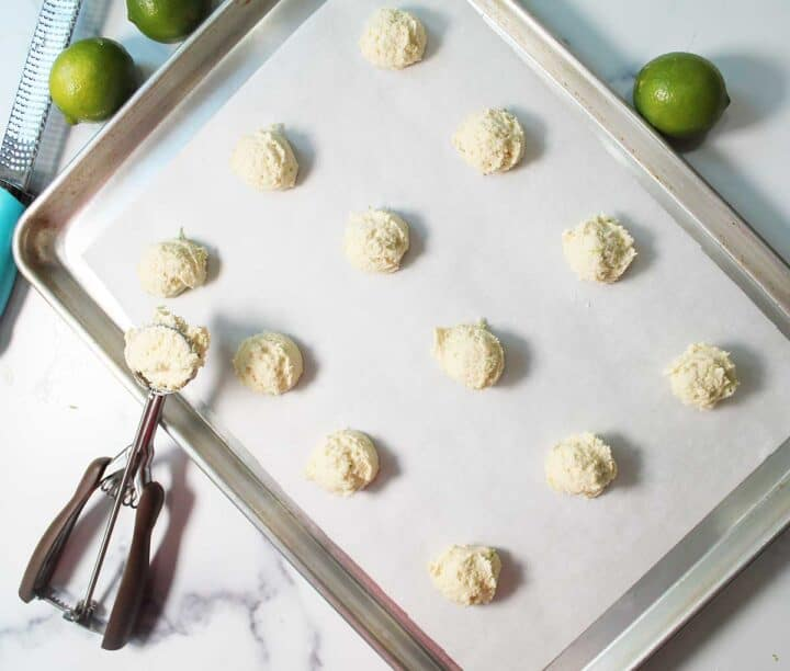 Scoops of lime cookies on a cookie sheet with scooper, zester and limes around it.