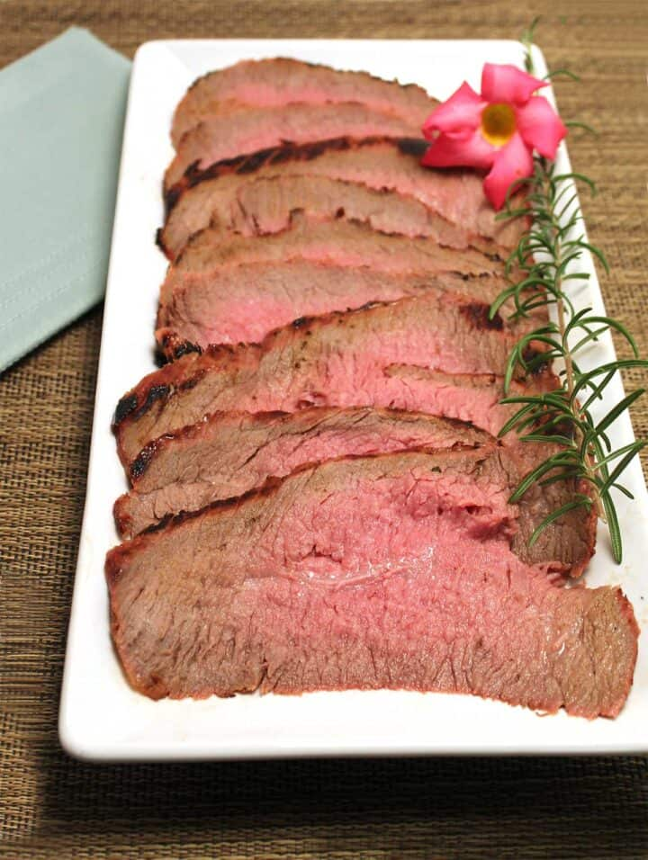 Sliced london broil on white platter with orchid.