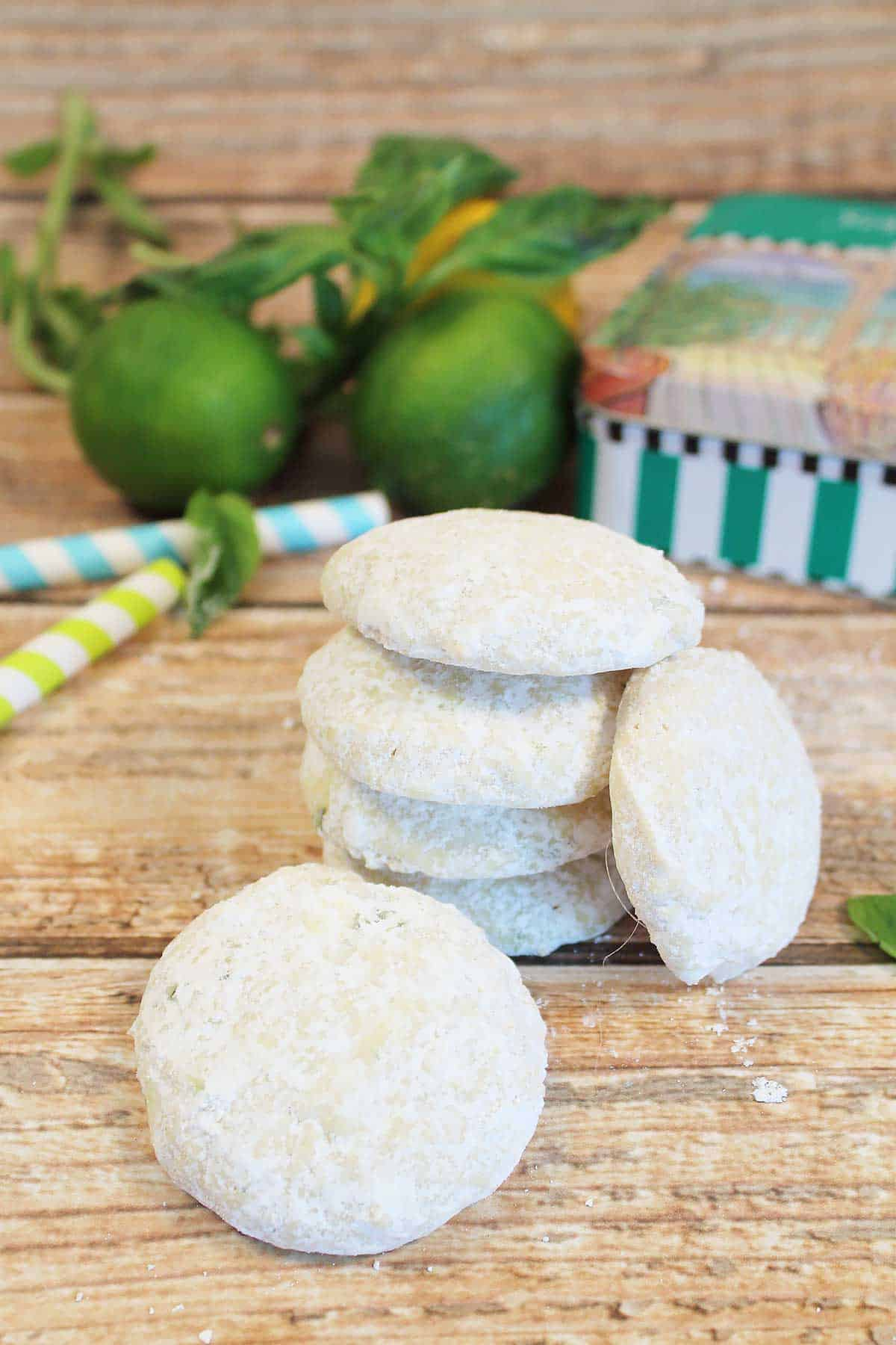 Stacked Key Lime Cookies on wooden table with limes and cookie tin in back.