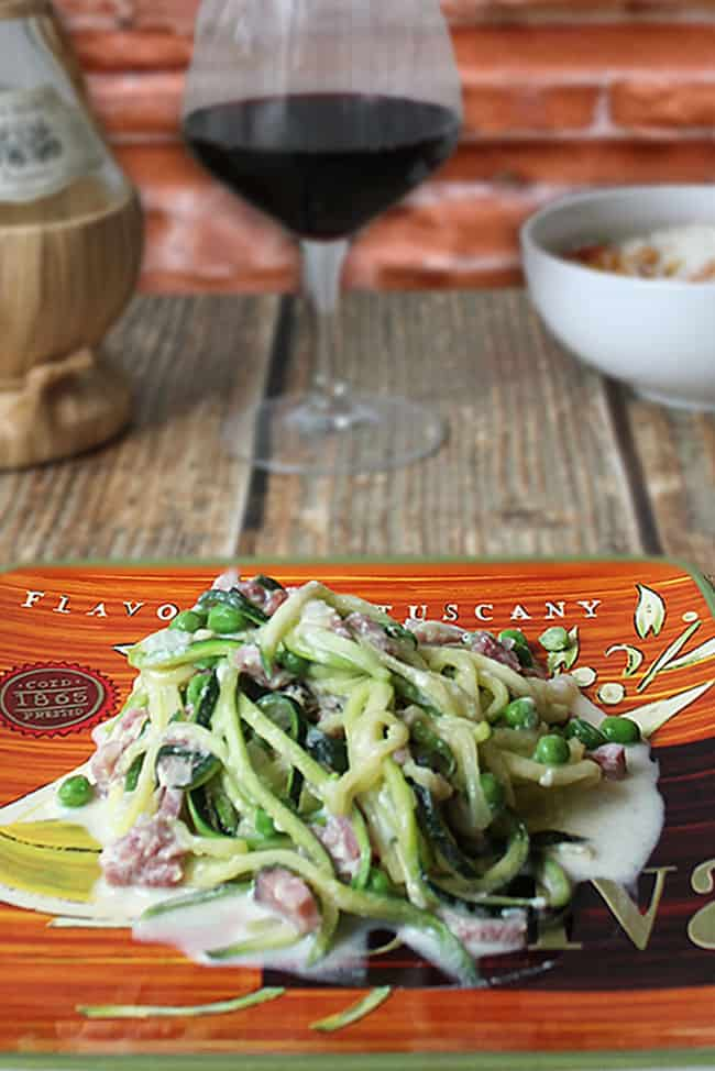 Zucchini noodles with cream sauce on Italian plate with wine in background.
