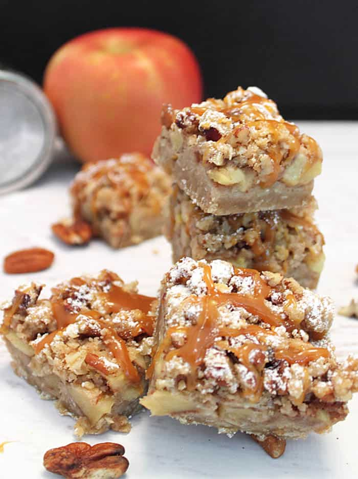 Cut apple pie bars with apples and powdered sugar in background.