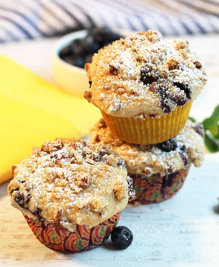 Stacked lemon blueberry muffins on white table with yellow napkin in background