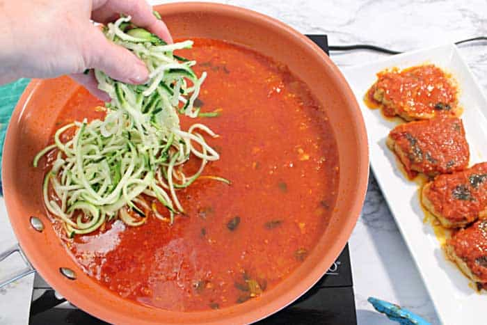 Tossing zoodles into pasta sauce.