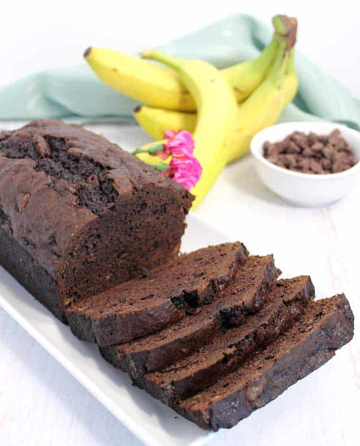 Sliced banana bread on white plate with bananas and chocolate chips in background.