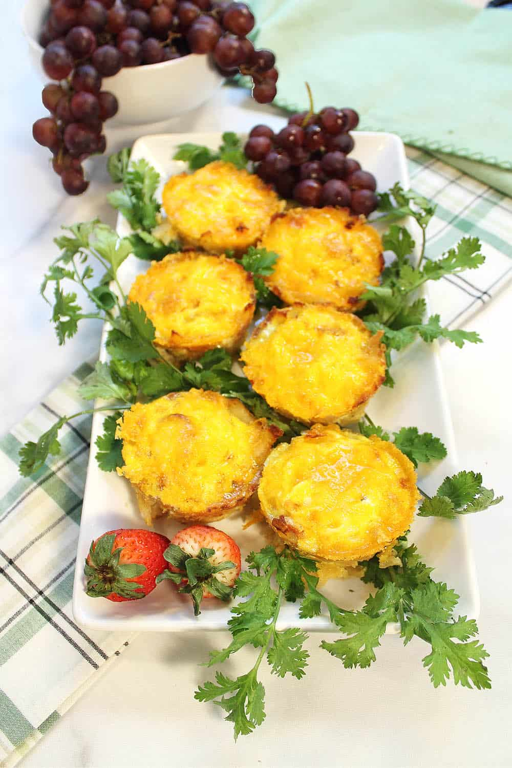 Egg muffins plated on green plaid napkin with grapes in background.