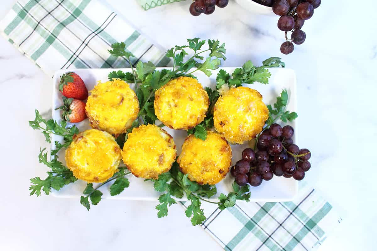Muffin Tin Eggs on white platter with parsley garnish and grapes.