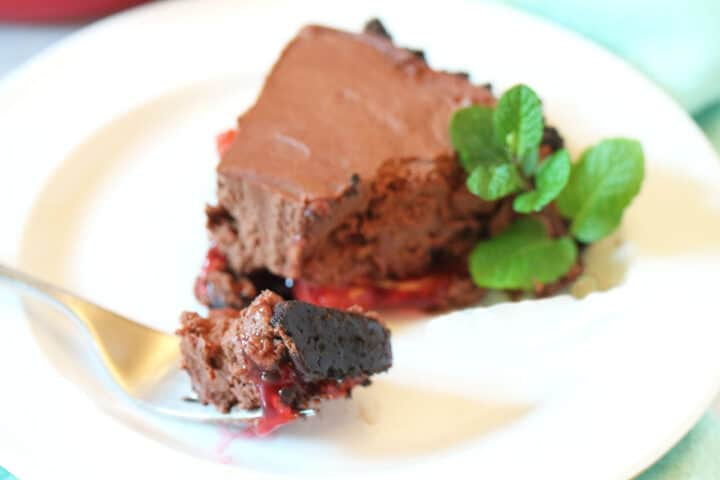 Plated slice of chocolate cherry pie with bite on fork.
