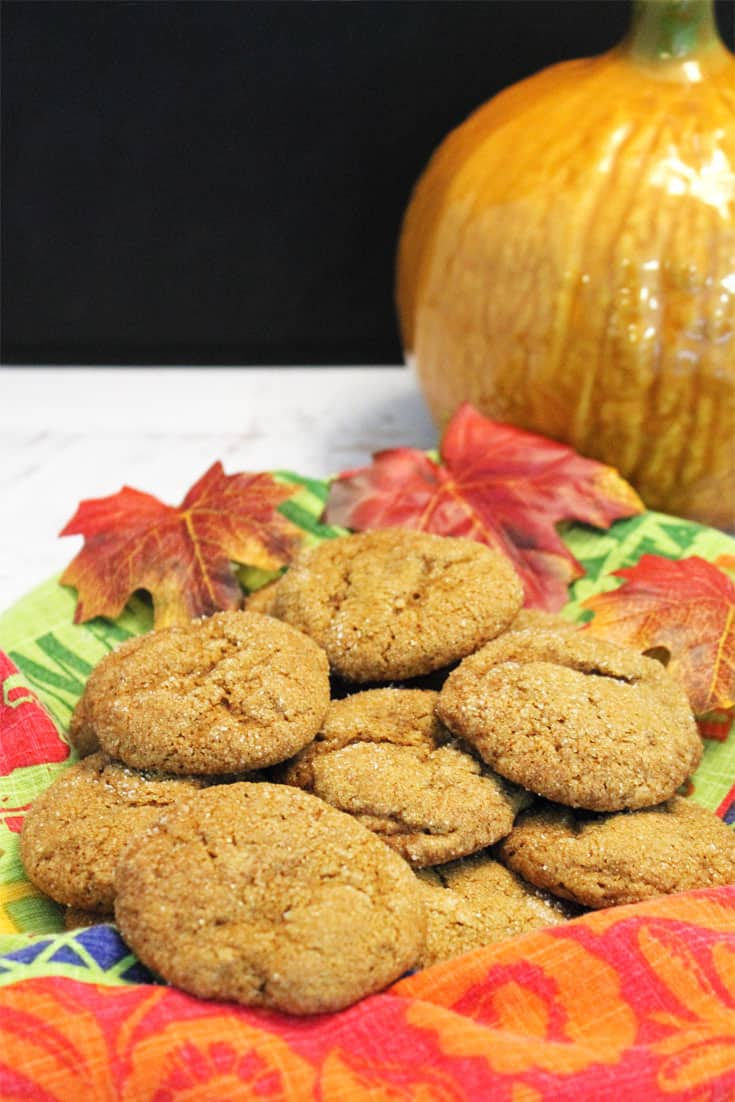 A basket of cookies lined with fall towel on white table with pumpkin in background.