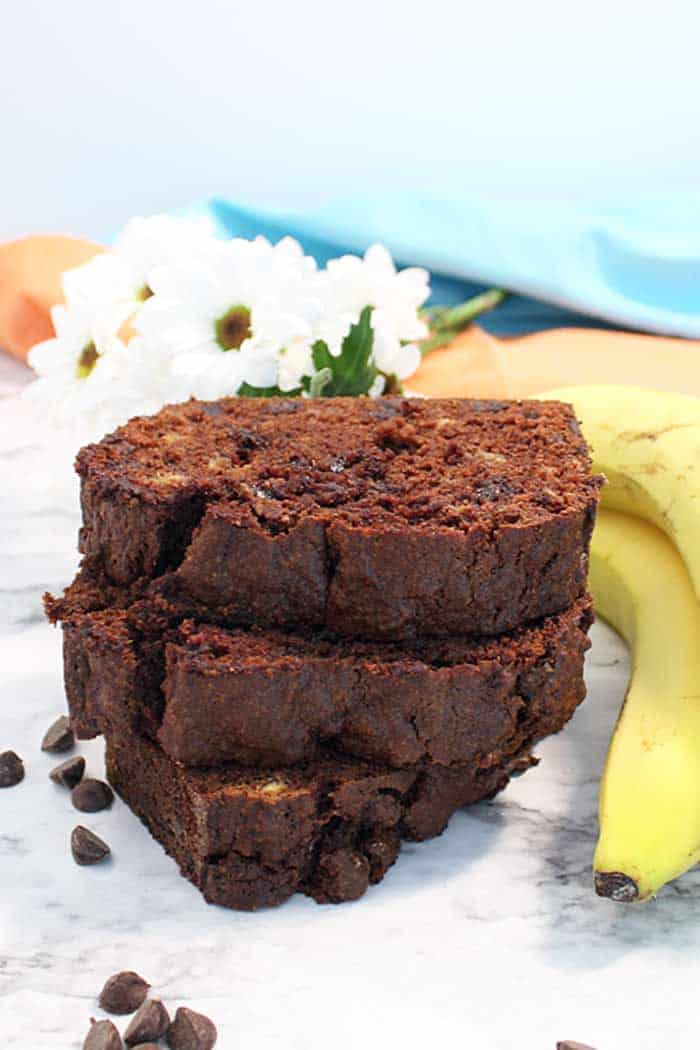 Stacked slices of chocolate banana bread next to bananas and daisies.