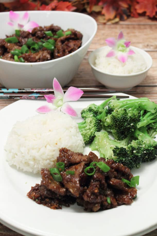 Plated Mongolian Beef with rice and broccoli with chop sticks.