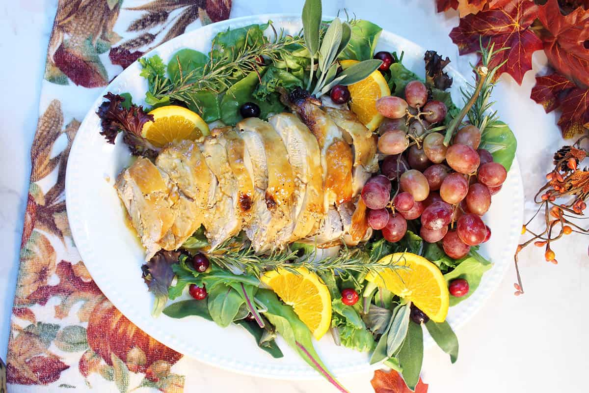 Overhead of sliced honey roasted turkey breast on platter with grapes and herbs.