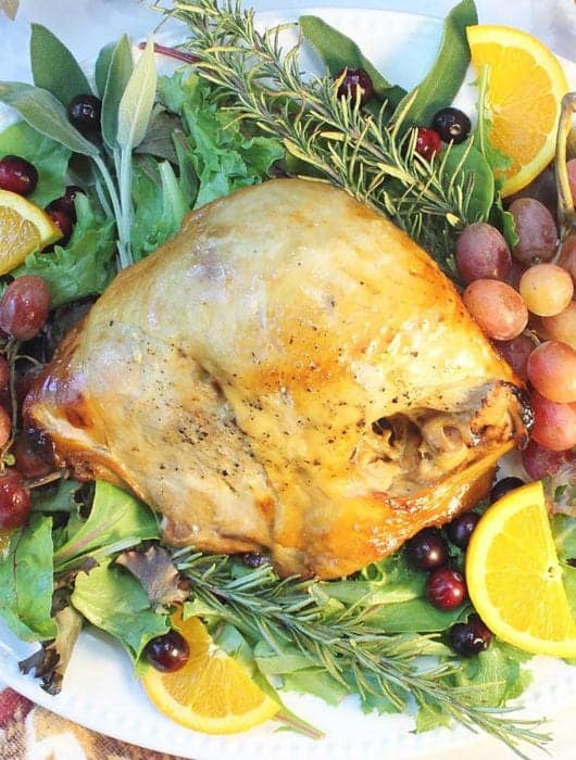 Overhead of turkey on white platter decorated with herbs and fruit.