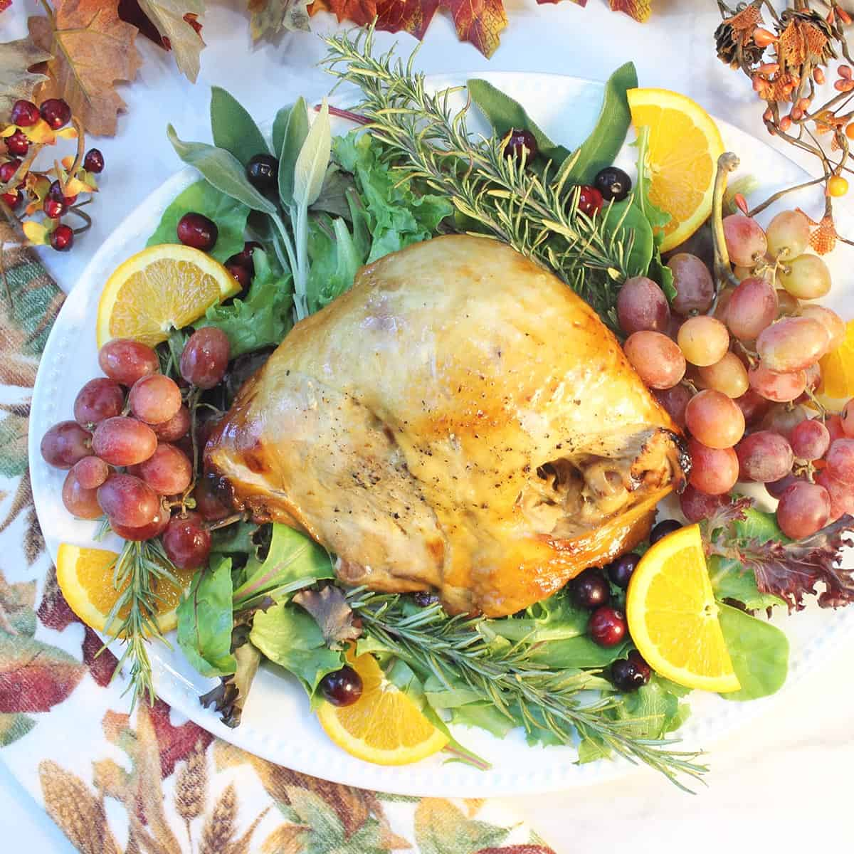 Overhead of roasted turkey breast on white platter decorated with herbs and fruit.
