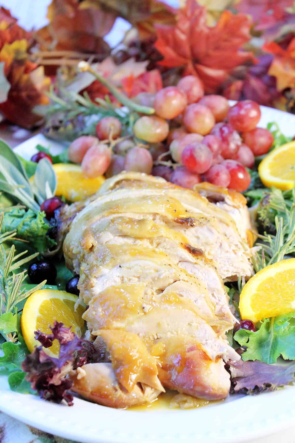 Sliced turkey on fruit decorated platter.