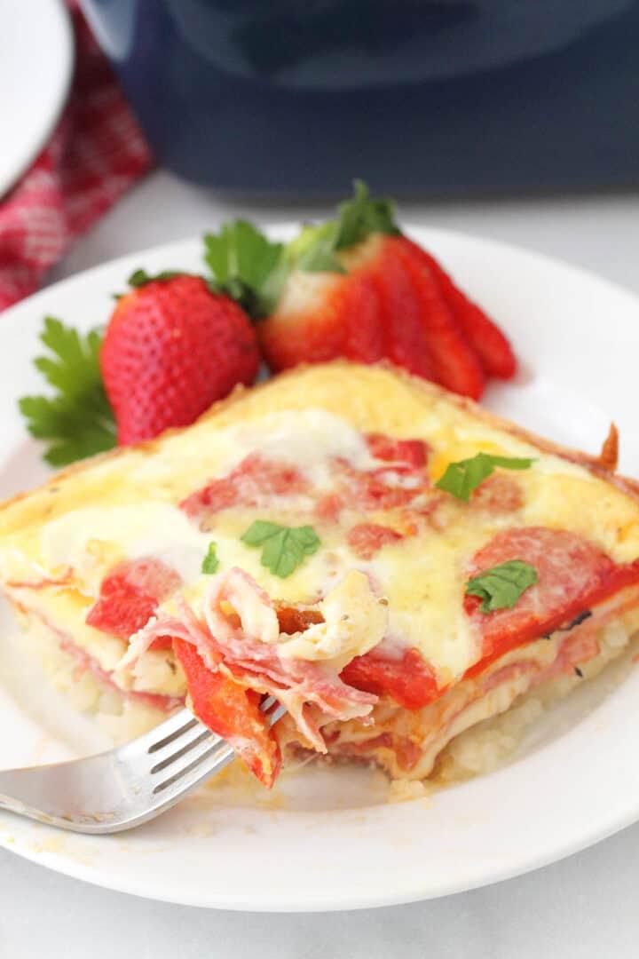 Italian Egg Bake on white plate with bite on fork and garnish of strawberries.
