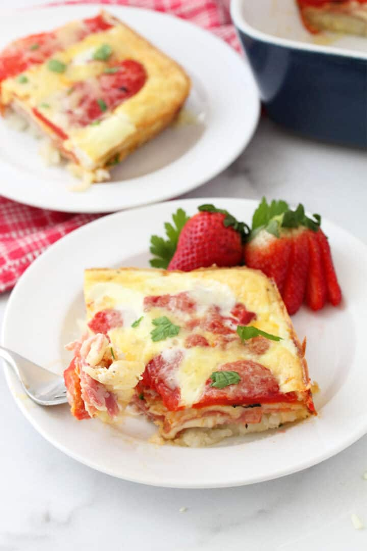 Two servings of Italian Egg Bake on white plates with casserole in background.
