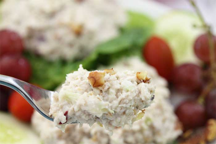 Bite of chicken salad with grapes on fork.