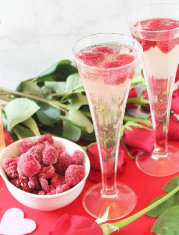 Two glasses of spritzer on red Valentine heart with rose and raspberries.