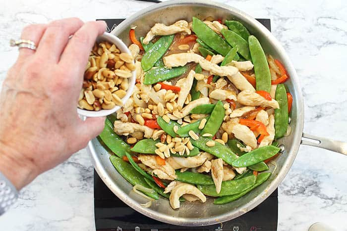 Adding peanuts to finished stir fry.