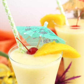 Closeup of top of glass filled with pina colada with mango.