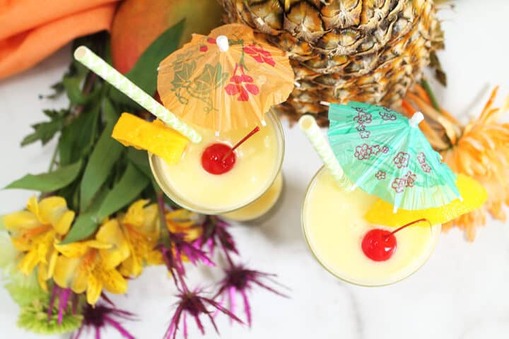 Overhead of cream of coconut cocktails by pineapples and flowers.