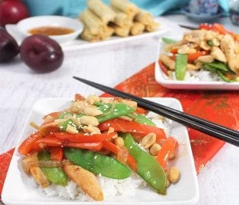 healthy chicken stir fry served for dinner on white plates with chop sticks.
